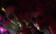 Black-light babes Nadia and Ophelia suck off a colorful cock